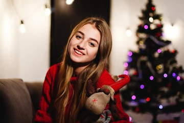 Christmas and New Year vibes. Home decorations. Charming young woman in red sweater sits on the couch before shiny Christmas tree and looks straight in the camera
