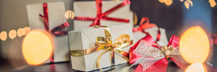Young woman is packing presents. Present wrapped in craft paper with a red and gold ribbon for christmas, birthday, mother's day or valentine BANNER, LONG FORMAT