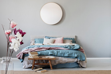 Classy round mirror on grey wall in stylish bedroom interior with warm bed with blue, pastel pink and beige bedding and wooden bench with books