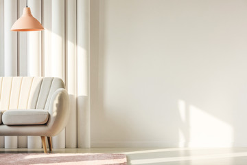 Copy space on empty white wall of birth living room with pastel orange lamp and white sofa