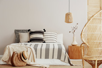 Copy space on white empty wall of bright trendy bedroom with flower in vase on wooden nightstand, king size bed with striped bedding and rattan peacock chair Fotoväggar