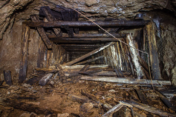 Underground abandoned gold iron ore mine shaft tunnel gallery passage wtih wooden timbering