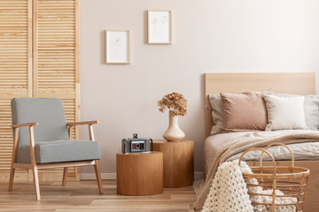 Trendy retro armchair next to two round wooden tables with vintage camera and vase with flowers in beige bedroom interior