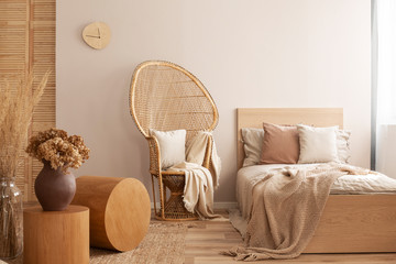 Peacock chair with pillow and blanket next to single bed with beige bedding and warm blanket, real photo