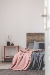 Grey and pink bedroom design with copy space on empty white wall