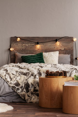 Cones on round wooden table in warm bedroom interior with king size bed with light bulbs on headboard