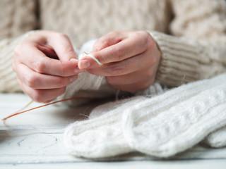 Woman knits winter warm clothes closeup
