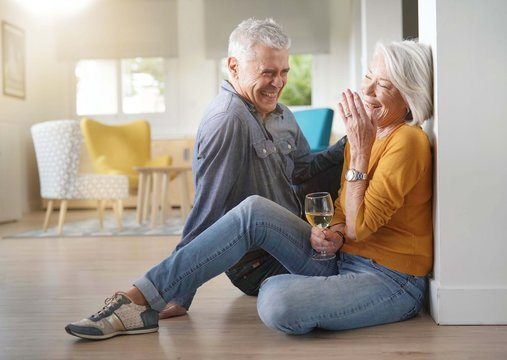 Relaxed senior couple sitting on floor in modern home with glass of wine