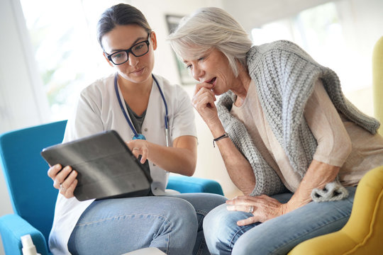 Doctor going through results and medication on tablet with senior patient