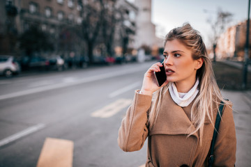 Attractive young woman talking on the smart phone in the city.