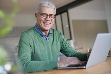 Modern senior man working on laptop at home