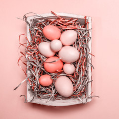 Eggs in a white tray. Creative Easter concept. Modern solid pink background.  . Living coral theme - color of the year 2019