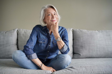Modern senior woman in all denim on couch