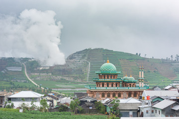 A village mosque appears in front of the rice fields and the sulphur exhausts of a volcano in Dieng Plateau, Central Java, Indonesia.