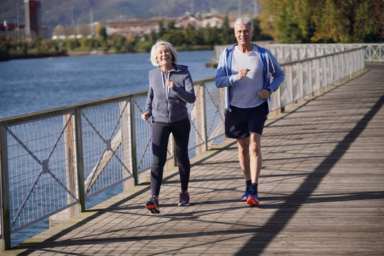 Active senior couple speed walking together on bridge