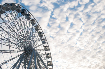 Part of ferris wheel over blue cloudy sky background in a fun park.