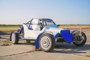 All-wheel drive off-road racing buggy car against the background of a light sky