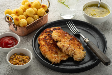 Wiener schnitzel with potato balls and lemon sauce. Chicken schnitzel in breading