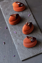 Contemporary Chocolate Violet Mousse Mini Cakes, on dark grey background.