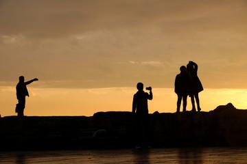 silhouette of people on bridge at sunset