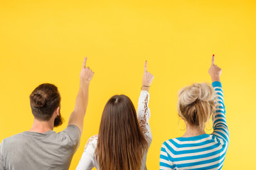 Back view of modern young people standing in row on yellow backdrop showing up with fingers