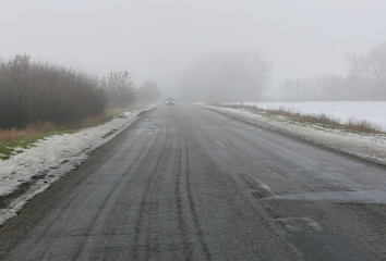 car goes on a bad road to fog