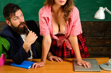 Sex education. Sexology teacher looks at sexy female student. Erotic education and sex Symbols on chalkboard. Anatomy lesson sex education in high school. Let's Talk Sex.