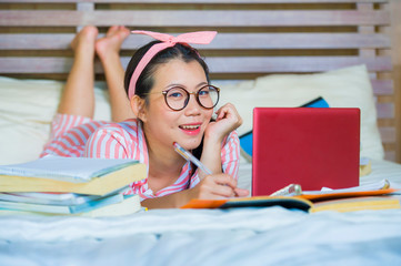 young cute and happy nerdy Asian Korean student teenager woman in nerd glasses and hair ribbon studying at home bedroom lying on bed with laptop computer
