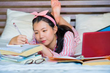 young cute and happy nerdy Asian Japanese student teenager girl in nerd hair ribbon studying at home bedroom sitting on bed with laptop computer and textbook
