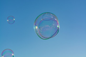 Many soap bubbles in air, blue sky, outdoor fun for everybody