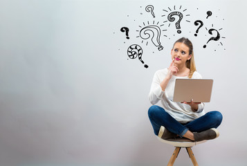 Question marks with young woman using her laptop on a grey background