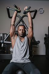 Black man exercising on machine in gym