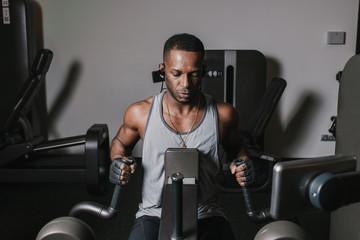 Black man exercising on machine in gym