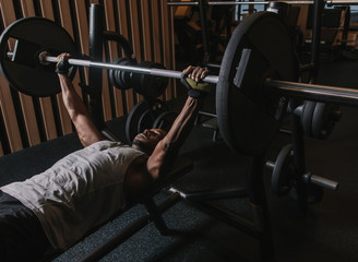 Black male lifting heavy barbell in gym