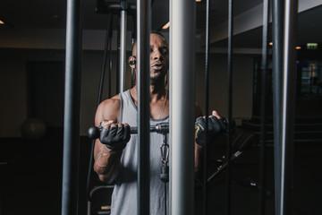 Black male doing exercise on machine