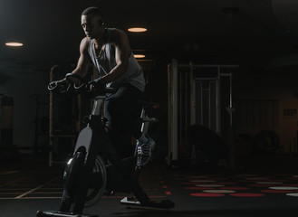 Serious black man on exercise bike in gym