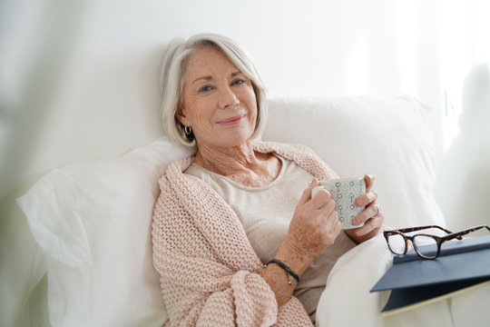 Beautiful senior woman relaxing in bed reading
