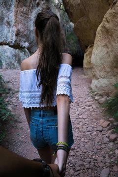 Una chica agarrando la mano de su novio mientras caminan por la montaña. La foto es realizada en la entrada de una cueva con colores marrones y verdes.