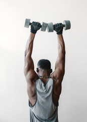 Black man with dumbbells in gym