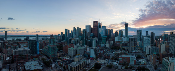 Aerial panoramic view of a modern cityscape of Downtown Toronto, Ontario, Canada, during a vibrant sunset.