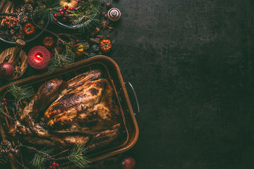 Whole roasted turkey, stuffed with dried fruits in roasting pan for Christmas dinner, served on dark table background with decoration and burning candles,  top view with copy space for your design