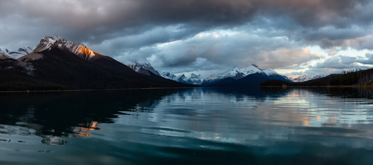 Panoramic Landscape View of a Glacier Lake during a Dramatic Cloudy Sunset. Taken in Maligne Lake, Jasper National Park, Alberta, Canada.