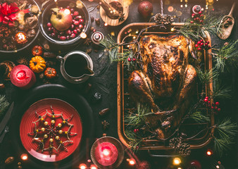 Christmas dinner table with whole roasted turkey, stuffed with dried fruits served in roasting pan with sauce,red plates, cutlery, decoration and burning candles,  top view. Traditional Christmas food