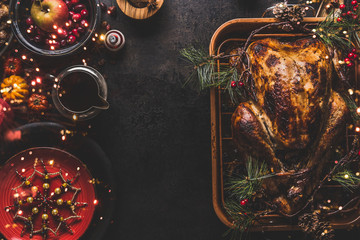 Christmas dinner table with whole roasted turkey, stuffed with dried fruits served with sauce,red plates, cutlery, decoration and burning candles,  top view. Traditional Christmas food. Copy space