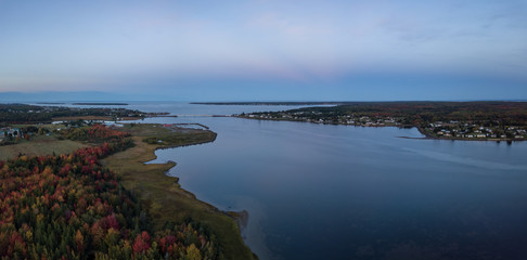 Aerial panoramic view of a bridge going across Cocagne River during a vibrant sunset. Taken in New Brunswick, Canada.