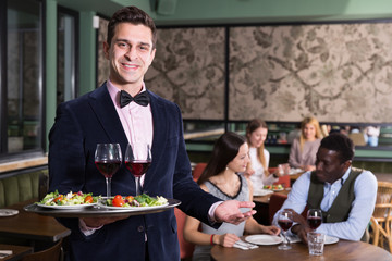 Smiling waiter with serving tray