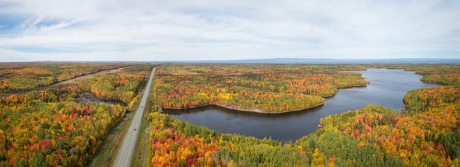 Aerial panoramic view of highway in a beautiful Canadian Landscape during fall color season. Taken near Belledune, New Brunswick, Canada.