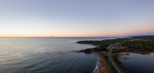 Aerial panoramic view of a Beautiful Sandy Beach on the Atlantic Ocean Coast during a vibrant sunrise. Taken near in Pabos Mills, Quebec, Canada.