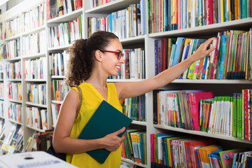 Cheerful female buying books in hard cover