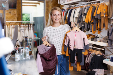Woman holding hanger with baby clothes in showroom